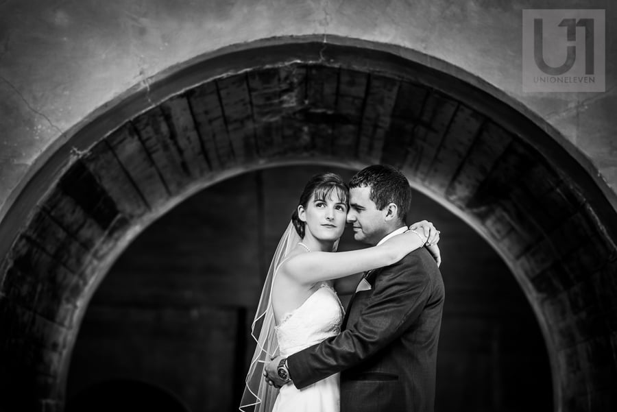 Black and white photo of a bride and groom standing in an embrace under an arch at the lochs in downtown Ottawa.
