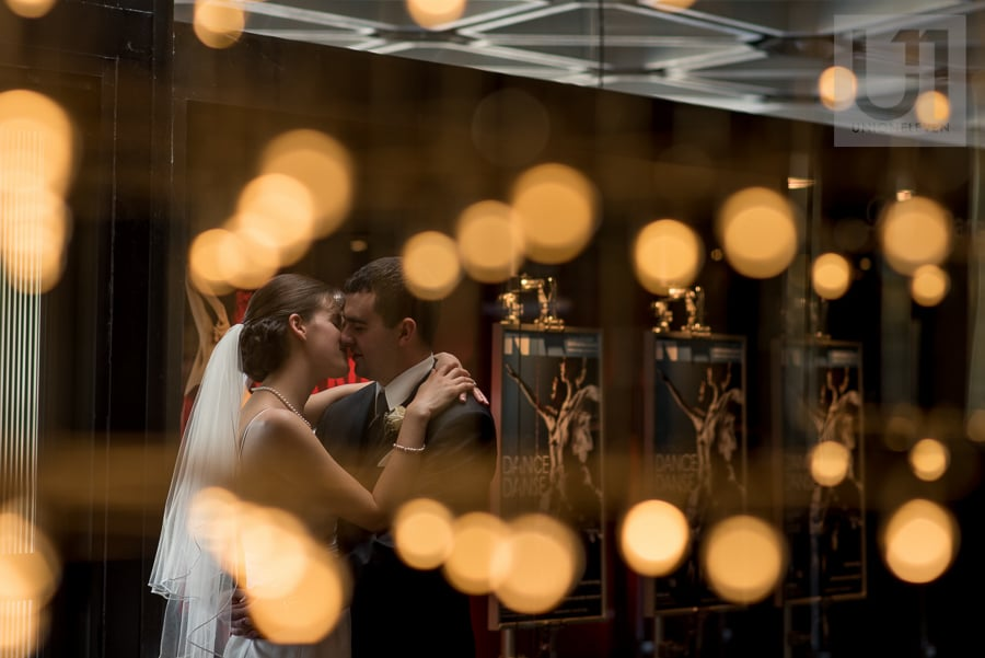 Bride and groom standing in an embrace, kissing each other inside National Arts Centre, with reflection of circular lights.