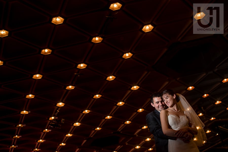 Groom hugging bride from behind, both smiling under a ceiling of spotlights at the NAC in Ottawa.