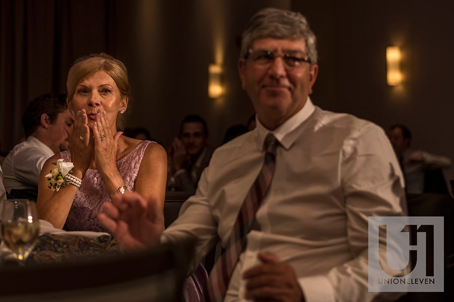 mom blowing kiss to couple during bride and groom speech at a le belvedere wedding