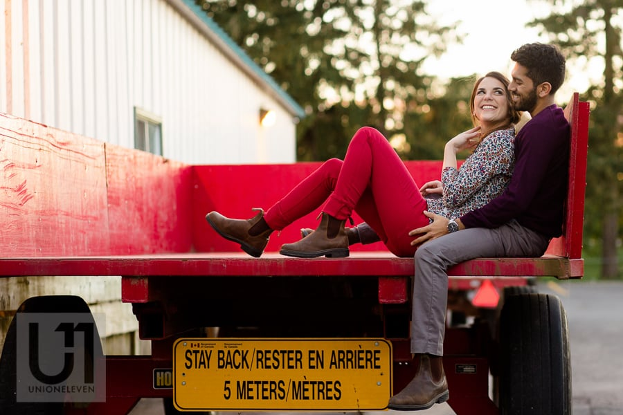 young couple sitting in an embrace on a red wagon at the Arboretum in Ottawa