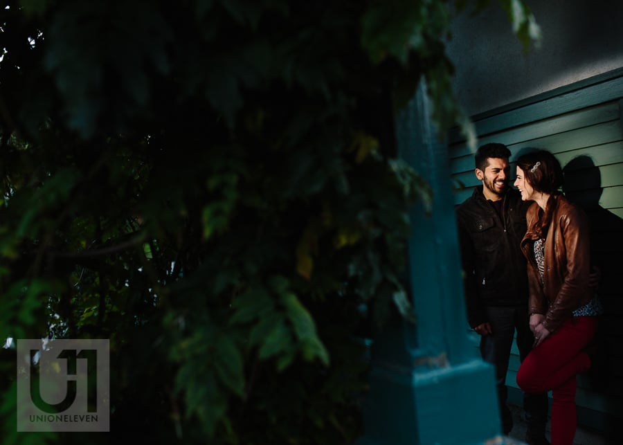 young man and young woman standing against a wall, looking at each other laughing in dark, evening light