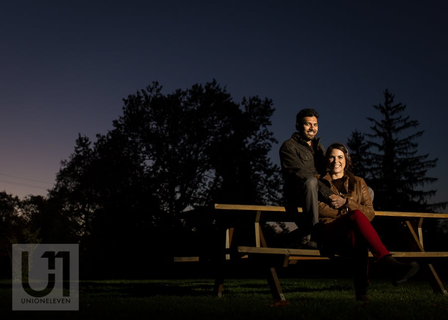 young man and woman sitting on a picnic table at the Arboretum in Ottawa, in dark evening light.