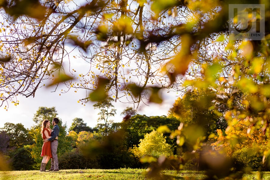 young couple standing in an embrace at the Arboretum, facing each other, with tree branches in the foreground