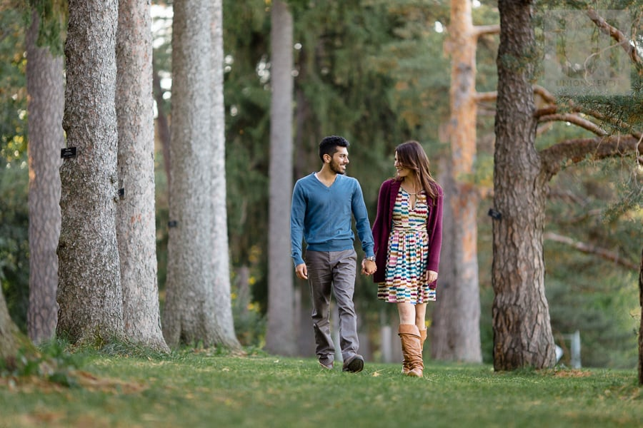 young man and young woman walking hand in hand in forest in Ottawa