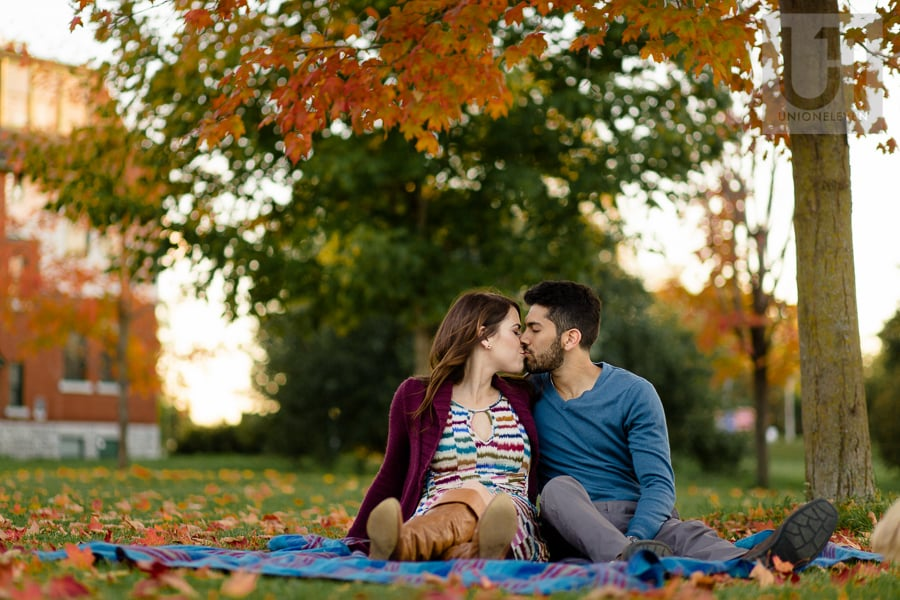 young couple sitting on blanket amidst fall trees, kissing