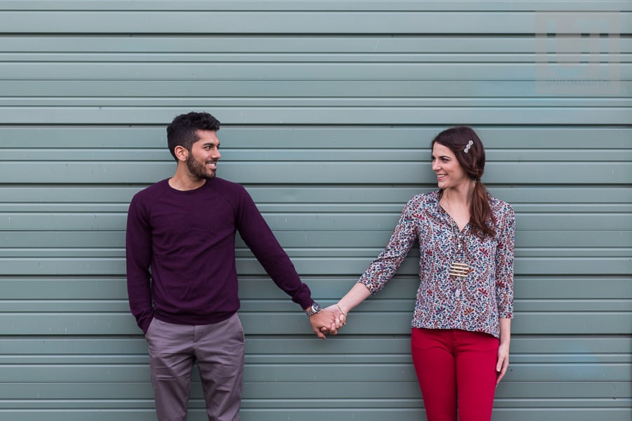 young man and young woman standing in front of slate grey wall while holding hands and looking at each other smiling