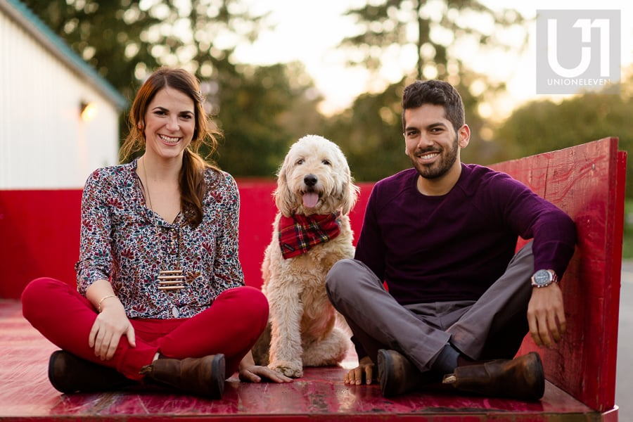 young couple sitting cross-legged on a red wagon with their golden doodle sitting between them, at Arboretum in Ottawa