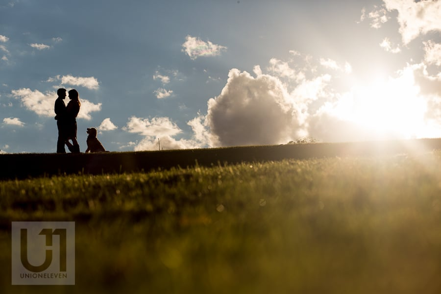 Silhouette of young couple standing in an embrace on a hill, with their dog sitting and facing them on the right.