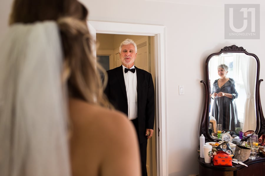 bride standing in room while her father stands in the doorway, seeing her for the first time; reflection of the bride's mother in mirror on the right side of the room.