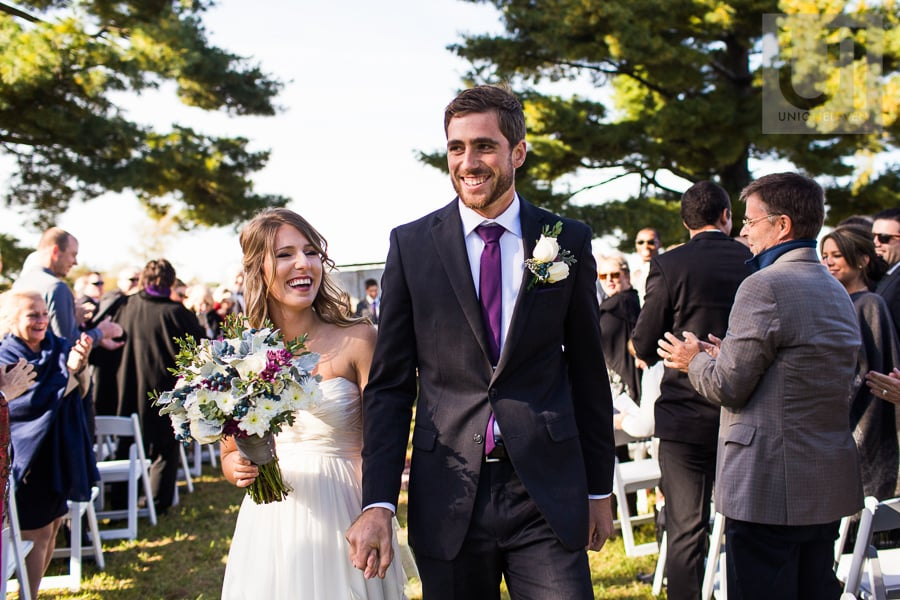 Bride and groom happily walking down the aisle, laughing after being announced husband and wife at wedding ceremony in Russell, Ontario.