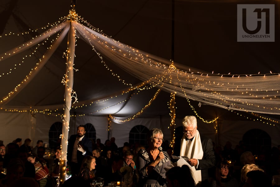 Older man and woman giving a speech during wedding reception, with draped fabric and twinkle lights hanging in the background,.