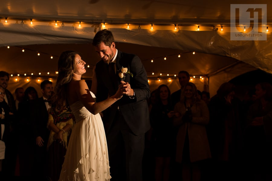 Bride and groom sharing first dance and laughing while their wedding guests watch under a tent lit by beautiful twinkle lights.