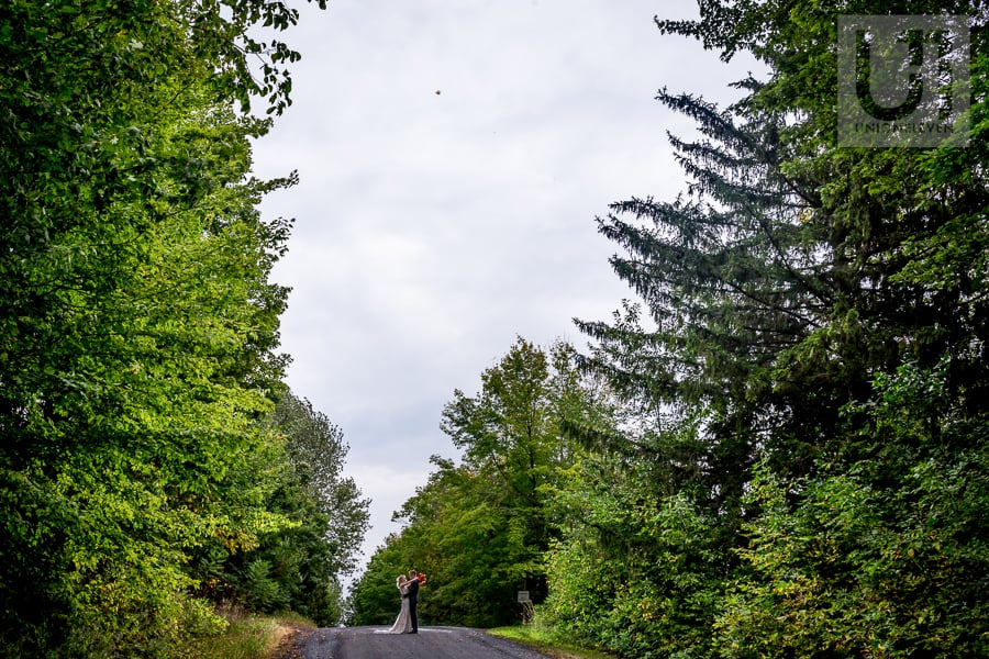 bride and groom standing arm in arm, facing each other on a gravel road amongst many trees near Strathmere, in Ottawa