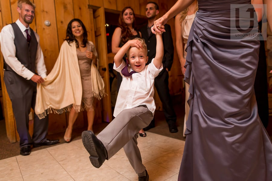 young boy dancing while holding bridesmaid's hand at wedding reception at Strathmere in Ottawa