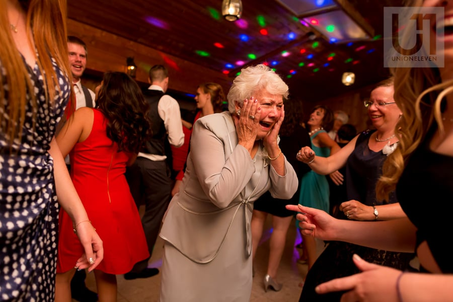elderly woman laughing with her hands on her cheeks while on the dance floor at wedding reception at Strathmere