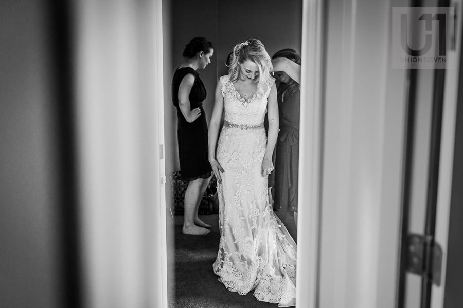 bride getting into her gown while two women help her, seen through a doorframe