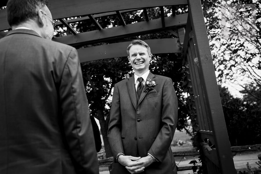 groom standing at end of aisle at Strathmere with a beaming smile, while he waits for his bride
