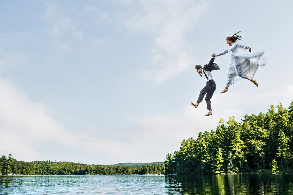 Bride and groom jumping into a lake with wedding atire on