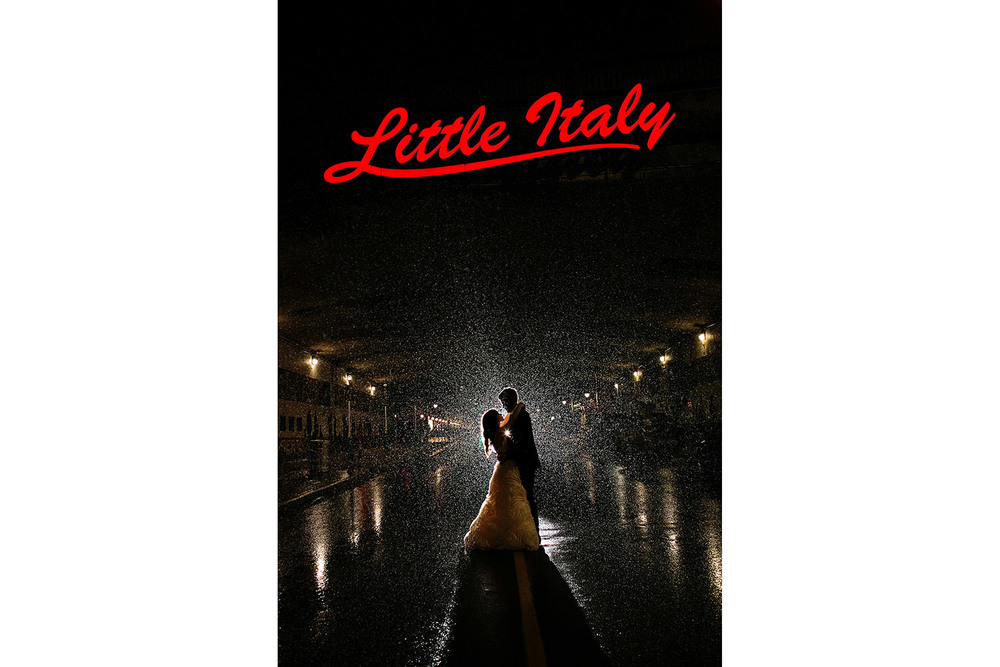 bride and groom pose in the rain underneath the little italy sign on preston street