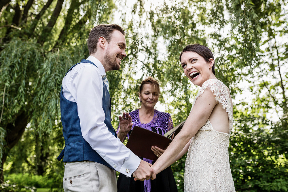 bride and groom reacting to vows during a wedding ceremony at experimental farm ottawa