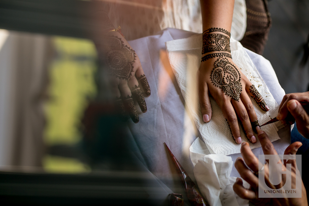 henna being applied to an indian brides hands