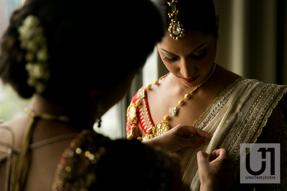 indian bride putting on her wedding dress