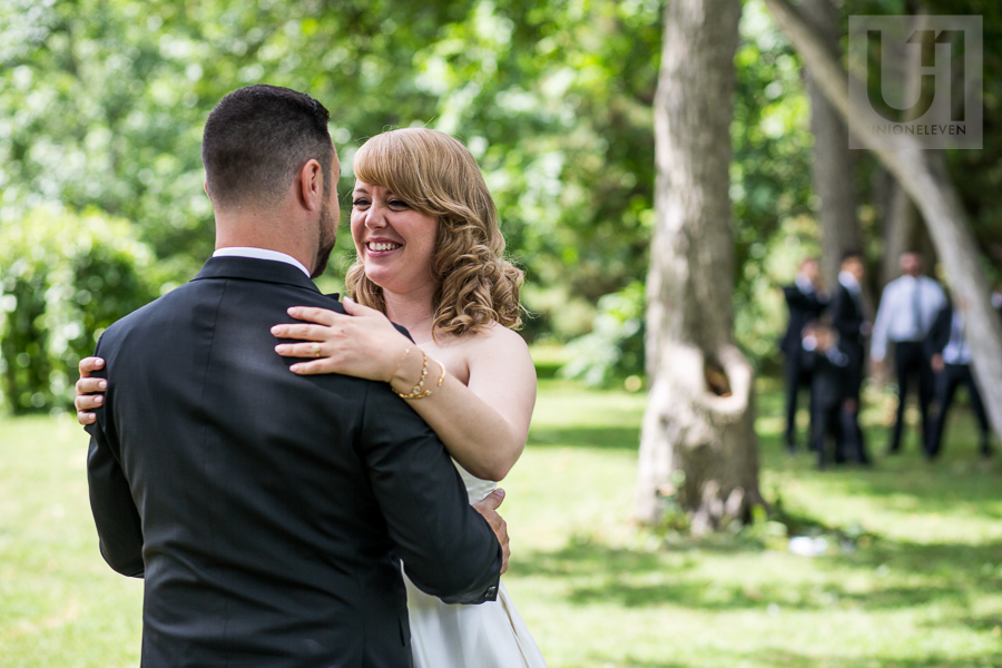 bride-smiling-embracing-groom-during-first-look-while-groomsmen-watch-in-distance