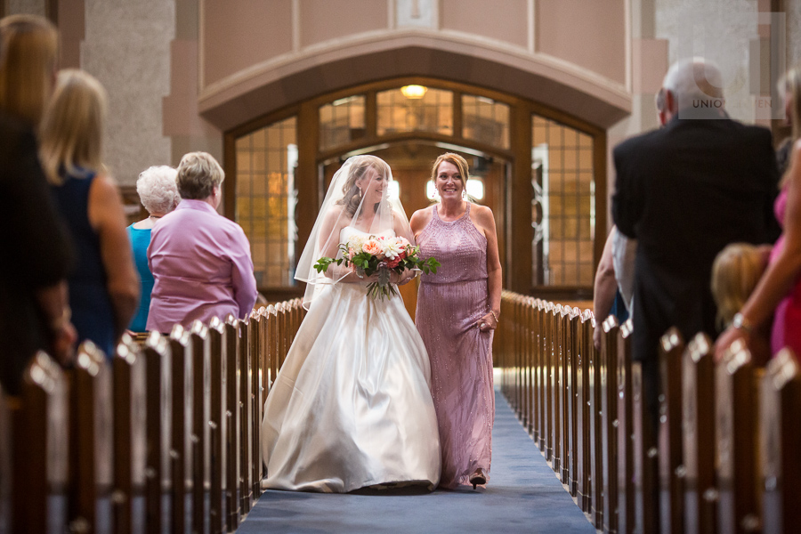 bride-laughing-while-walking-down-church-aisle-with-mother-at-ottawa-wedding