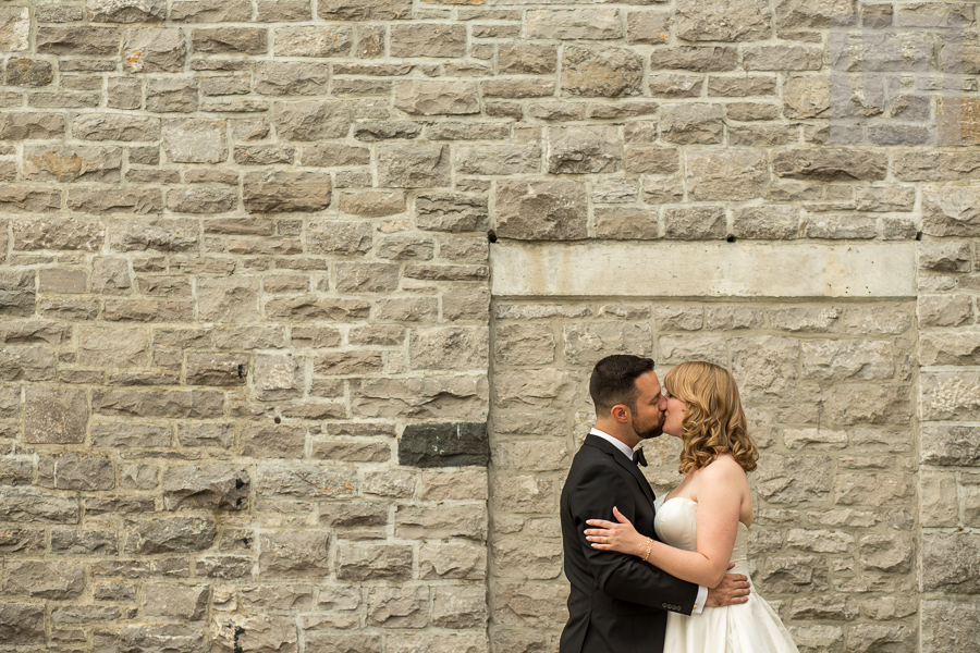 bride-and-groom-kissing-in-front-of-stone-wall-in-downtown-ottawa
