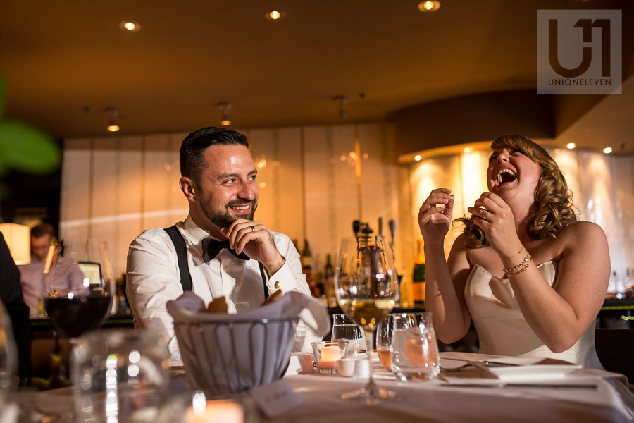bride-and-groom-laughing-reaction-to-speech-during-wedding-reception-at-eighteen-restaurant-in-ottawa