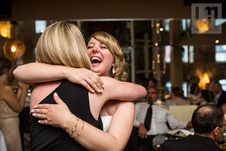 bride-smiling-and-hugging-female-guest-during-wedding-reception-at-eighteen-restaurant-in-ottawa