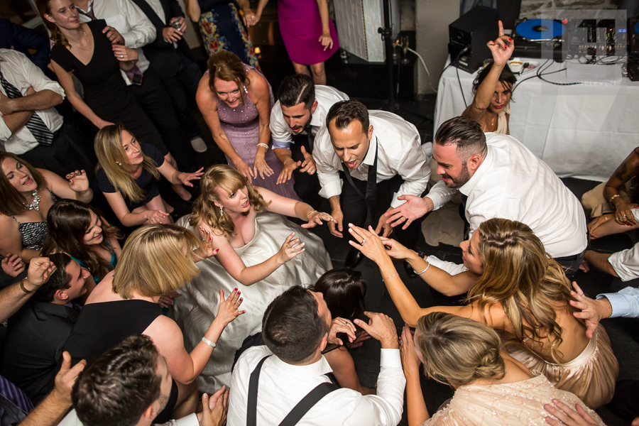 bride-groom-and-their-guests-getting-low-on-the-dance-floor-during-wedding-reception-at-eighteen-restaurant-in-ottawa