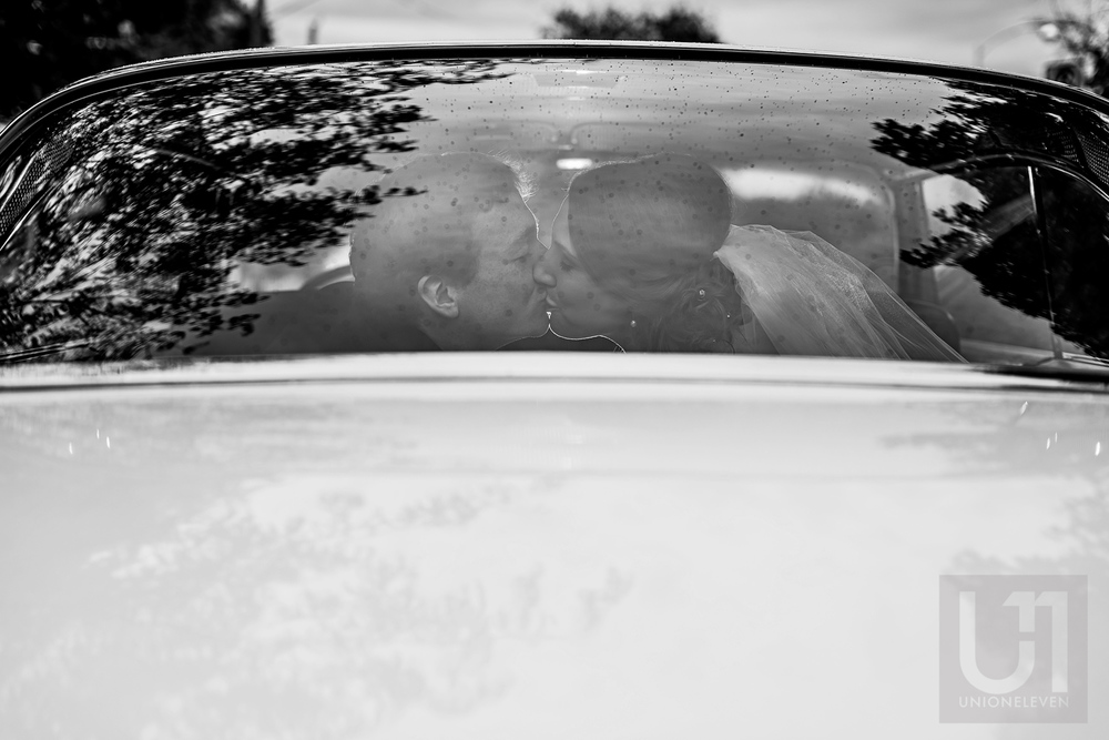 The bride and groom sharing a kiss on their car ride leaving the ceremony