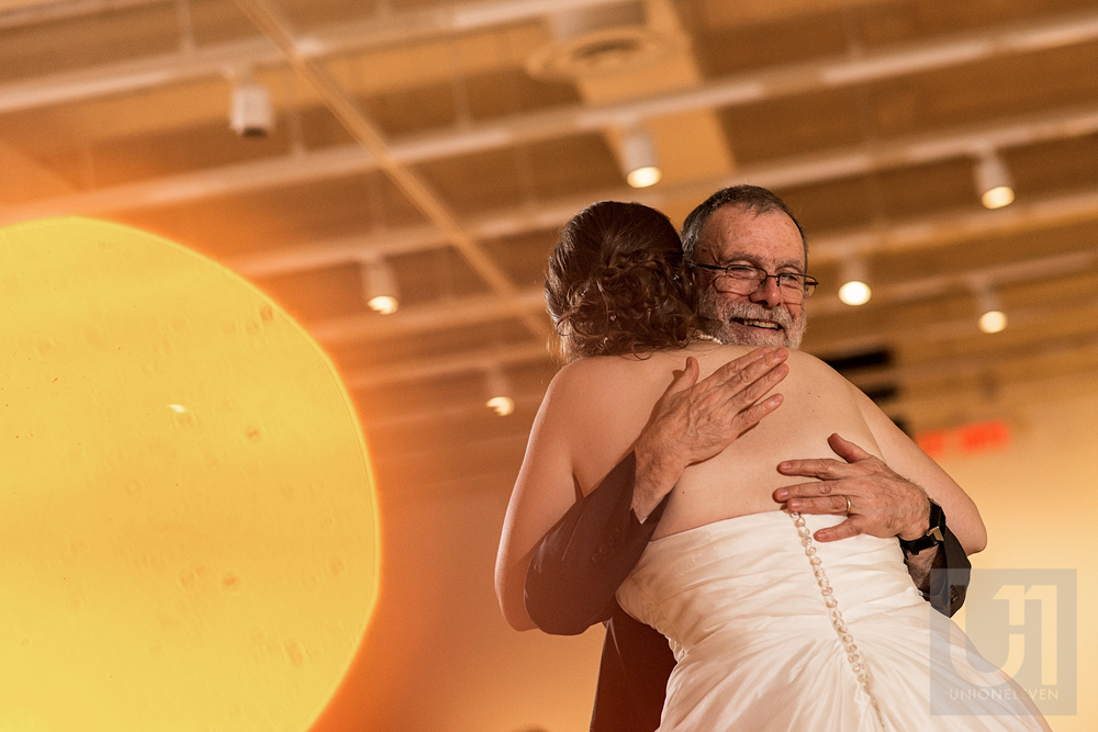 A photo of a hug between the bride and her father at the wedding reception