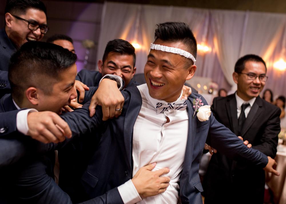 The groom with his groomsmen wearing the bride's garter