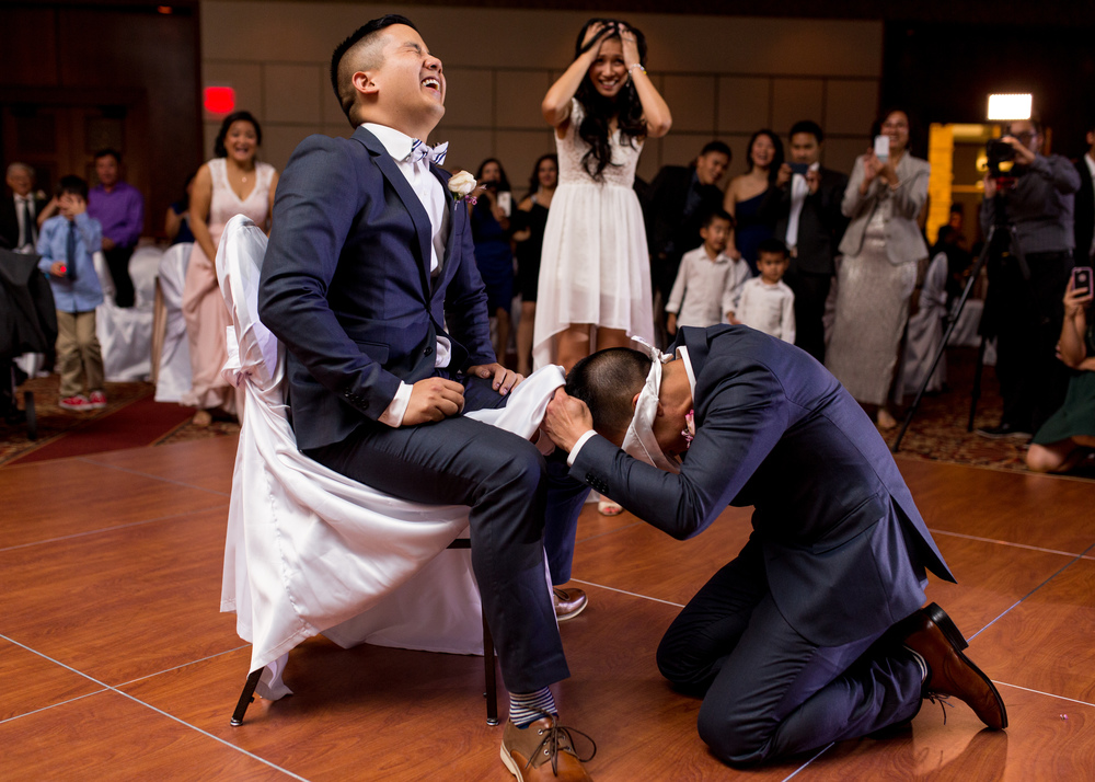 Groom and his groomsman playing a wedding garter game