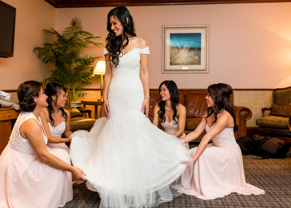 Bride and her bridesmaids helping her with her wedding dress
