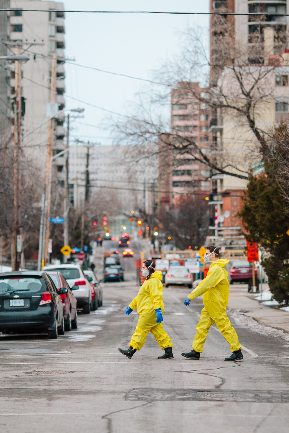 Engagement shoot with the couple crossing the street dressed in hazmat suits