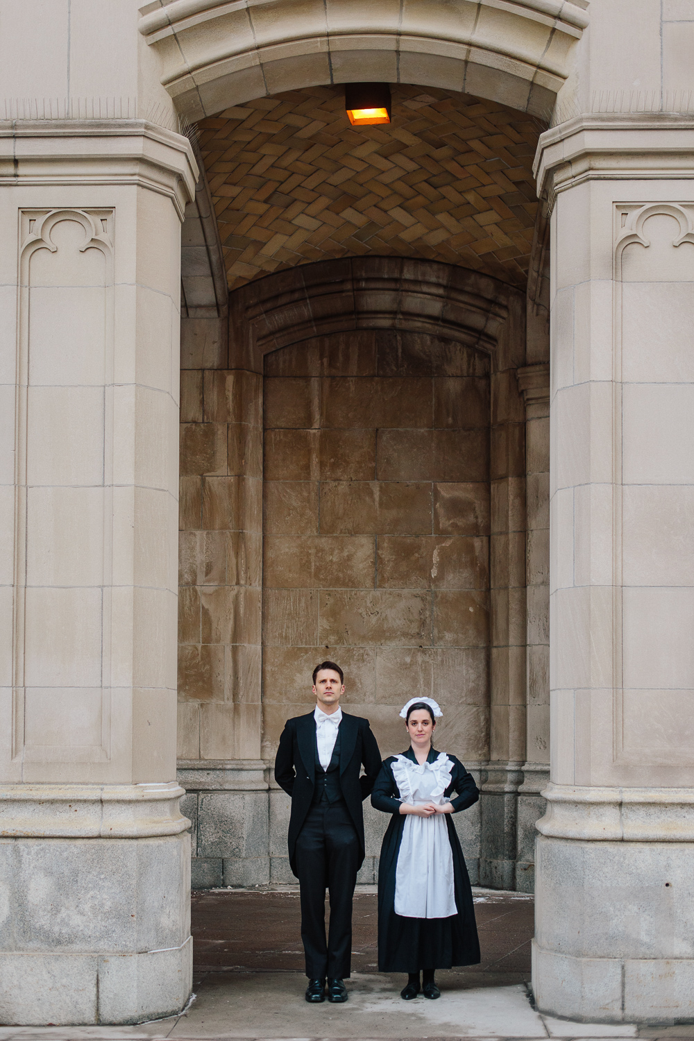 Engagement shoot of the couple posing in front of stone pillars dressed as a butler and maid