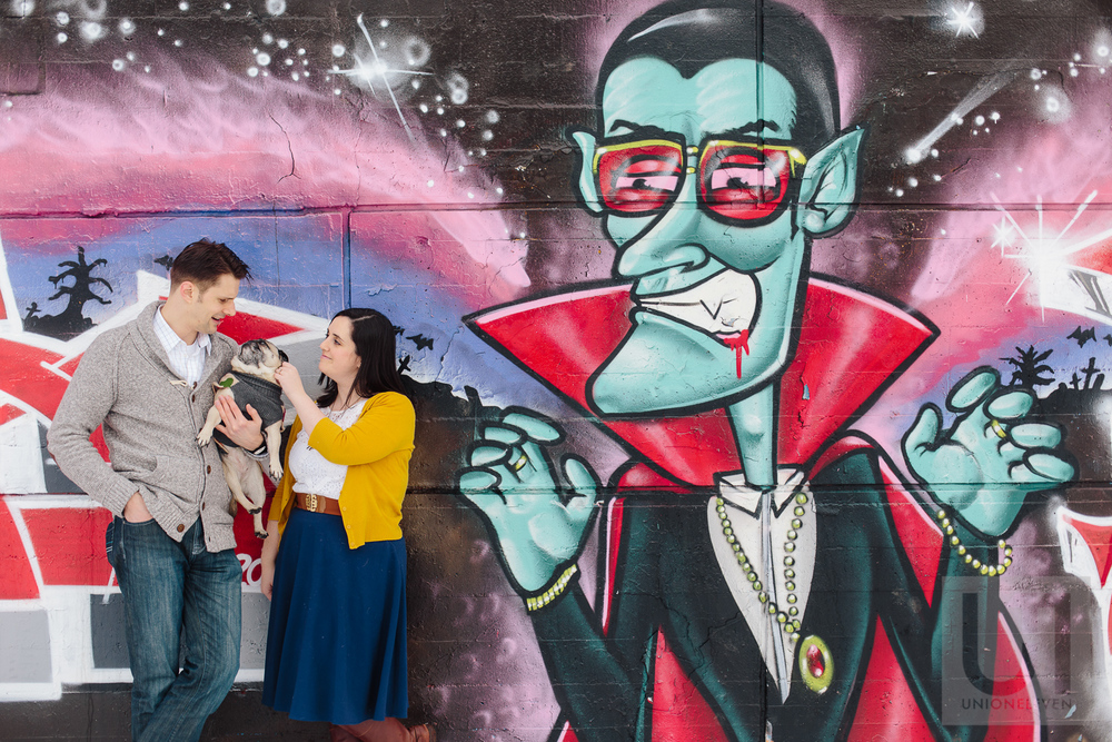 Engagement shoot with the couple and their pug in front of a graffiti wall in Ottawa