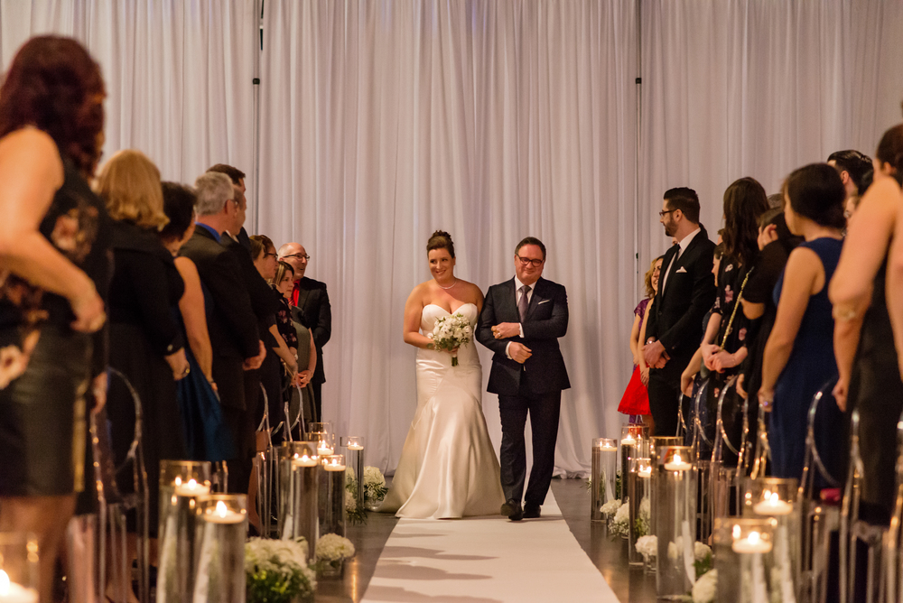 The bride being walked down the aisle with her father