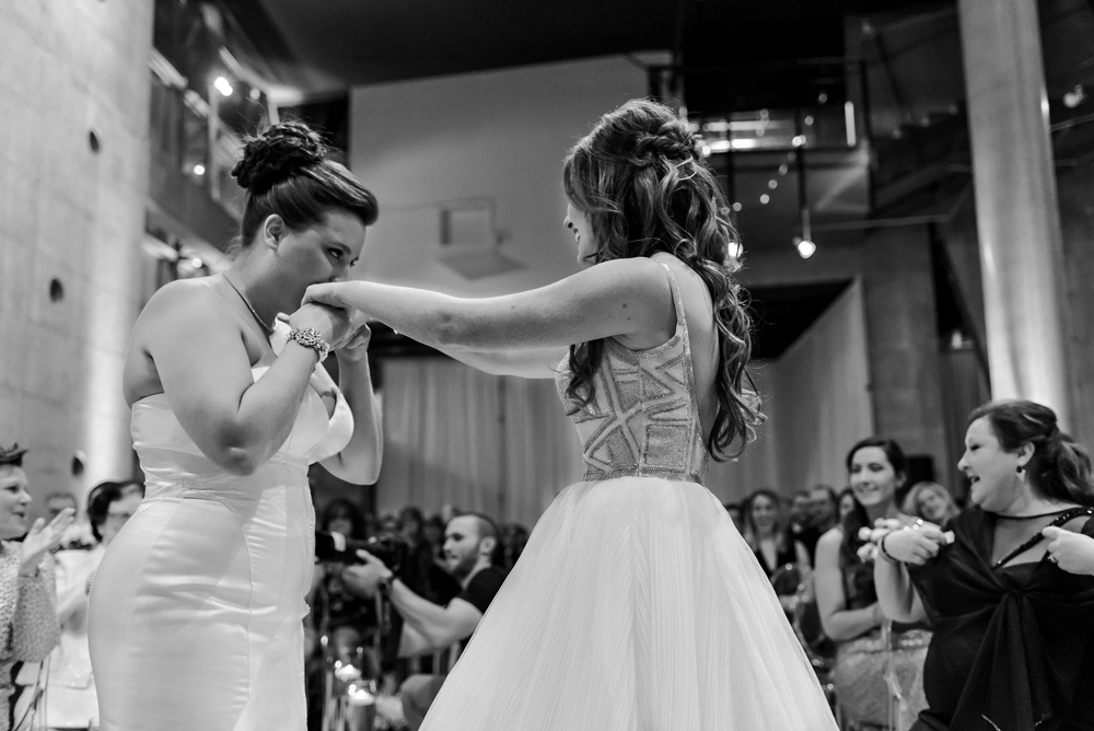 A photo of the two brides during their ring exchange