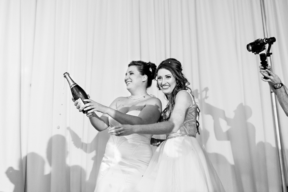 The brides opening a bottle of champagne to start their wedding reception
