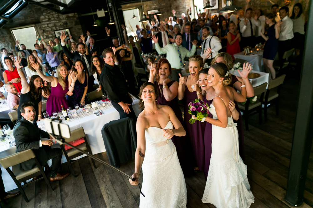 The brides and their bridesmaids taking a selfie