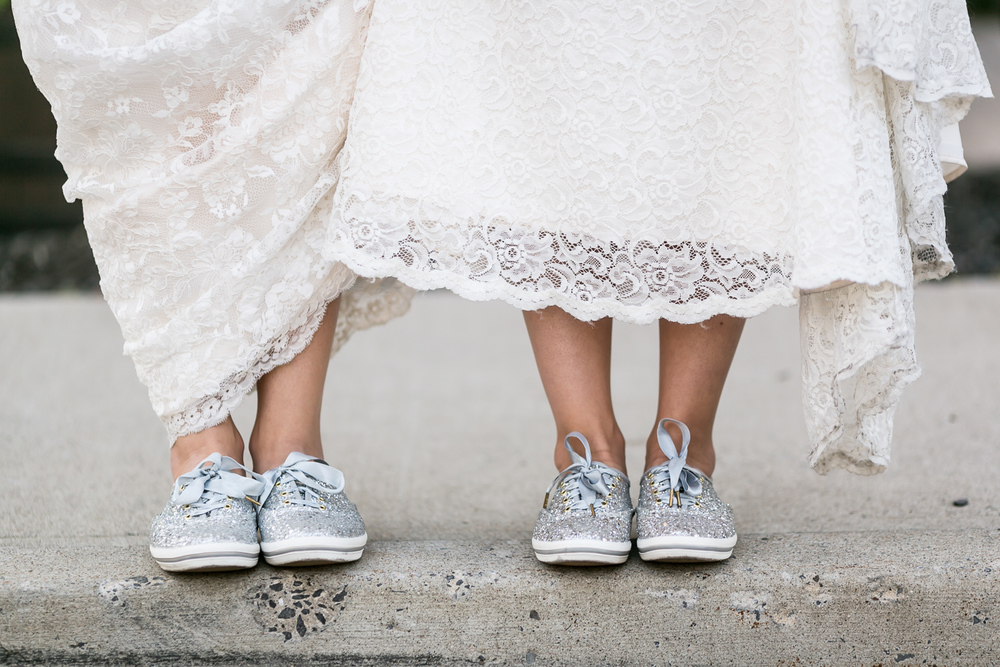 A photo of the brides showing off their matching sequinned tennis shoes