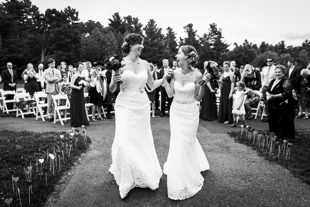 The brides walking hand in hand back down the aisle after their wedding ceremony