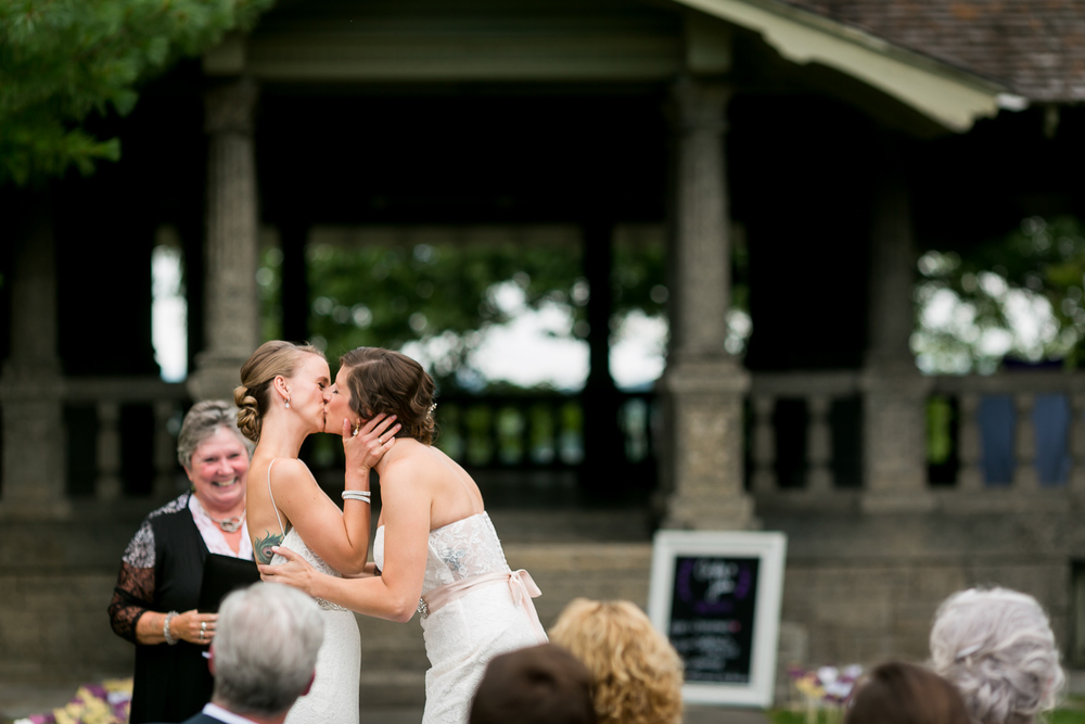 The brides sharing their first kiss during their wedding ceremony