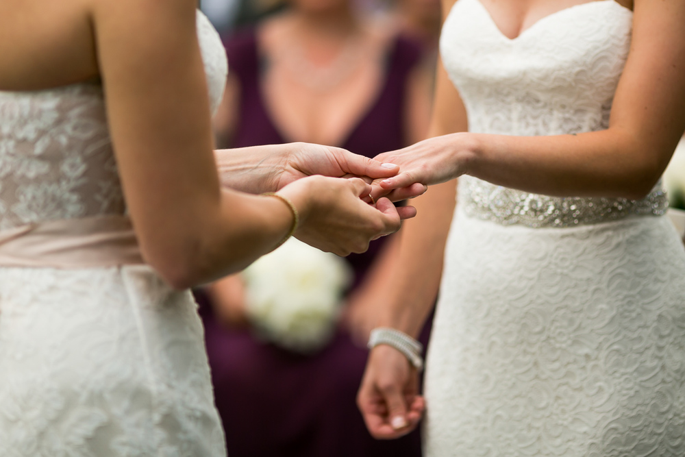 The brides exchanging their rings during their wedding ceremony
