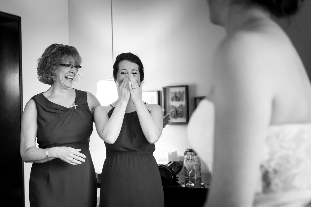 A bridesmaid and the mother of the bride seeing the bride in her dress for the first time